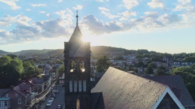 日没時のペンシルベニア州ベツレヘムのパノラマの景色。フリッツ記念ユナイテッドメソジスト教会。パノラマカメラの動きを持つ空中ドローンビデオ, 太陽の前を通過する塔と. - プロテスタント点の映像素材/bロール