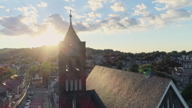 panoramic scenic view of bethlehem, pennsylvania, at sunset. fritz memorial united methodist church. aerial drone video with the panoramic camera motion, with the tower passing in front of the sun. - bethlehem pennsylvania stock videos & royalty-free footage