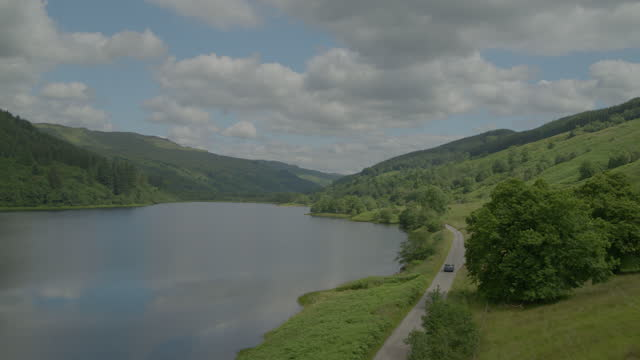 panoramic shot of a car driving along loch fyne - pasture stock videos & royalty-free footage