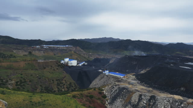 panoramic view left to right across a large open cast coal mine that feeds and powers baogang iron and steel plant in baotou inner mongolia china mining trucks move coal spoil and slag - land mine stock videos and b-roll footage