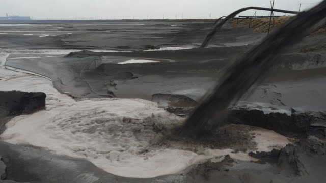 panoramic view left to right across the radioactive toxic tailings lake at the rear of the baogang iron and steel plant in baotou china the lake is full of heavy metals and rare earths and over 10km wide - water pollution stock videos & royalty-free footage
