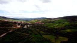 Panoramic view of a village in a valley in Morocco near the Atlas mountains, under cloudy sky.