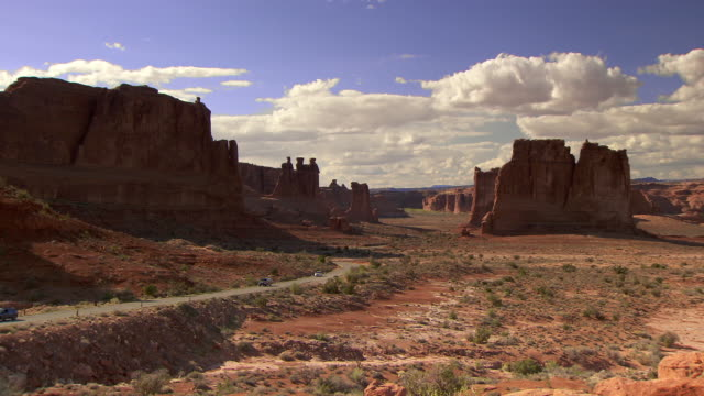 Panoramic view of Arches National Park with tourist cars driving in distance - zoom in towards cars
