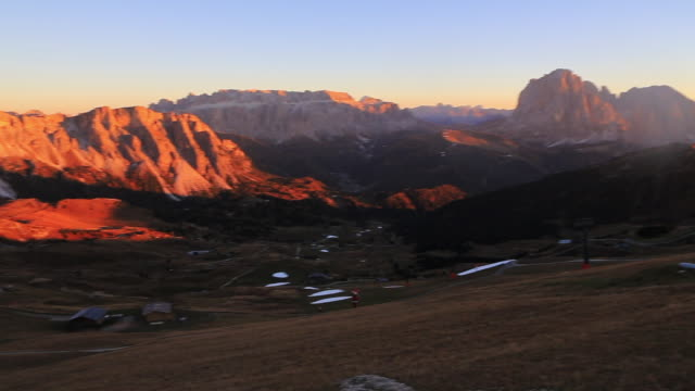 Panoramic view of the beautiful Dolomites mountains on the top of the Seceda mountains at dusk.