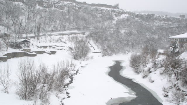 panoramic view of the historic town of veliko tarnovo and the frozen river yantra covered by snow - osteuropäische kultur stock-videos und b-roll-filmmaterial