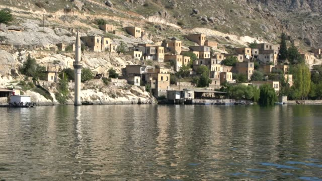 panoramic view of the town of eski savaşan köyü (old savaşan köyü), partially submerged under the rising waters of the birecik dam on euphrates river, southeast turkey - village stock videos & royalty-free footage