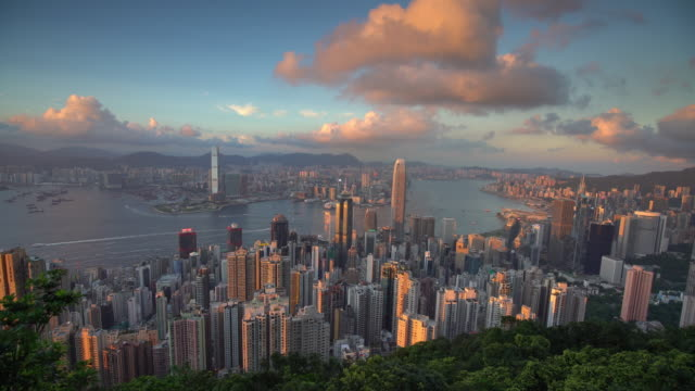 panoramic view of victoria harbor and hong kong skyline in china at sunset - victoria hong kong stock videos & royalty-free footage