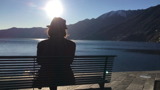 panoramic view over a woman with hat sitting on a bench and enjoy the sun over alpine lake with mountain - オーバーコート点の映像素材/bロール