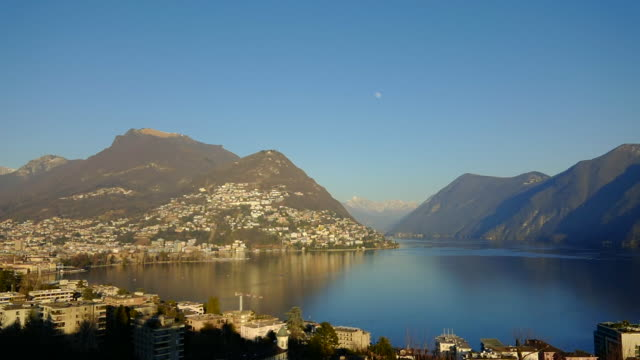 panoramic view over city and alpine lake lugano with mountain and the moon - ticino canton stock videos and b-roll footage