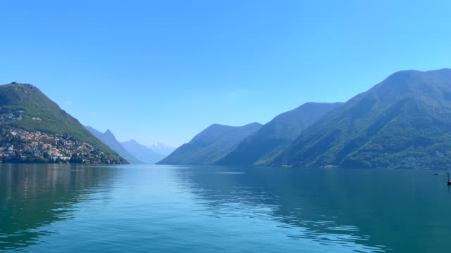 panoramic view over city of lugano and alpine lake and mountain in a sunny day - sunny video stock e b–roll