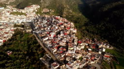 Panoramic view over Moulay Idriss in a valley in Morocco, under the sun.