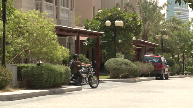 panright from a villa in the al garhoud residential district as a resident leaves his home on a motorbike - intercontinental hotels group stock videos & royalty-free footage