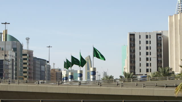 pan-right from saudi flags fluttering in the breeze. - riyadh stock videos & royalty-free footage