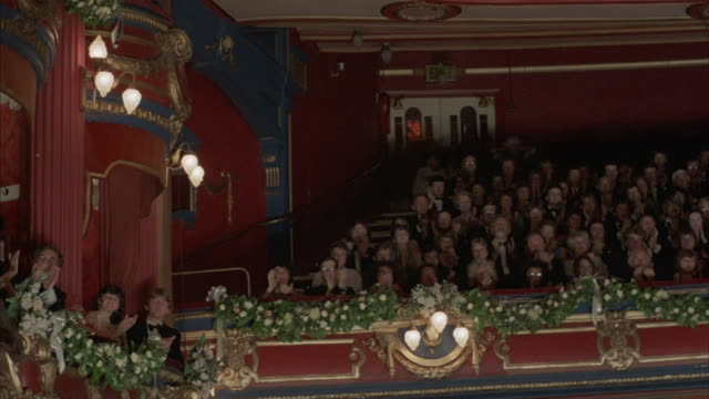 Pan-right of an audience in the upper tiers of an ornate theater giving a standing ovation.