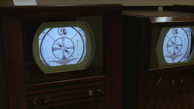 Pan-right of five vintage televisions showing test patterns.