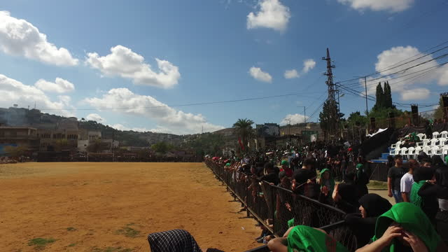 pan-right of the sports field and audience waiting to watch the reenactment of the battle of kerbala at the ashura commemoration in nabatieh. ashura... - ashura muharram stock videos & royalty-free footage
