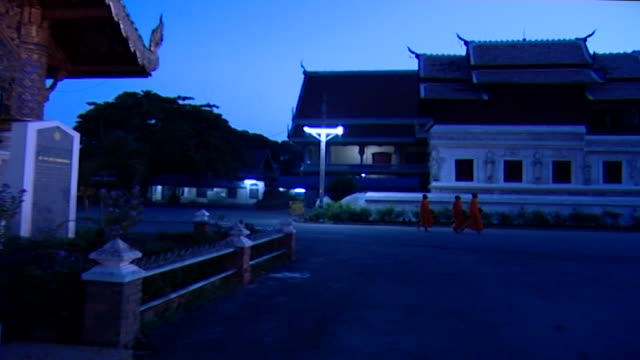 pan-right on buddhist monks, in kasayas, leaving the temple compound, carrying almsbowls, to conduct pindacara, or alms rounds; a daily ritual for... - theravada stock videos & royalty-free footage