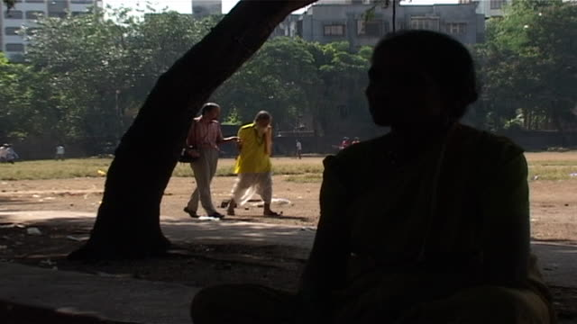 pan-right on two indian men strolling through a park in mumbai chatting. one is wearing a traditional dhoti with prayer beads while the other is in... - dhoti video stock e b–roll