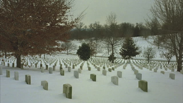 Pan-right shot across rows of white headstones at a military cemetery in winter.