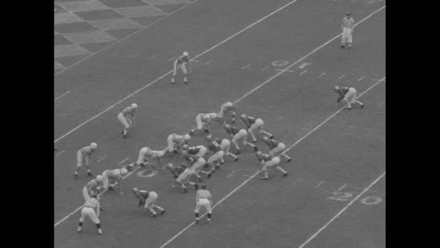 pans across tulane stadium and field formations during pre-game festivities at sugar bowl / #27 delbert shofner, baylor bears halfback, runs up... - クオーターバック点の映像素材/bロール