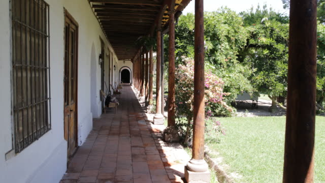 panshot of a sunny garden in the backyard on a property in calera de tango chilethe arch creates shadows and on the left side are wooden doors calera... - christian ender stock-videos und b-roll-filmmaterial