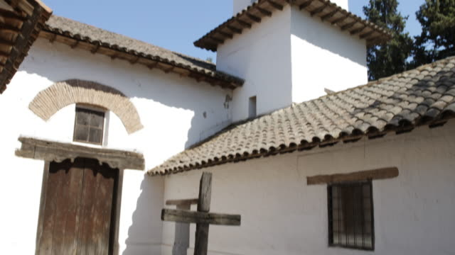 panshot of a wooden cross standing in the backyard of a jesuit church in calera de tango chile the house facade is painted white and the house has a... - jesuit stock videos and b-roll footage