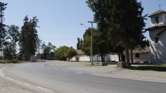 panshot of the area in front a a community college in calera de tango chile the road runs in front and is surrounded by a view trees calera de tango... - jesuit stock videos and b-roll footage
