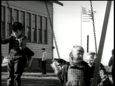 panther creek school children swinging on swings fg w/ wooden schoolhouse bg. teacher standing by school ringing bell for end of recess, children... - schoolhouse stock videos & royalty-free footage