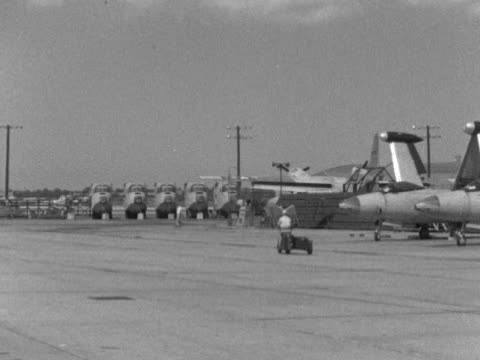 Panther jets w/ wings folded up lined up outside at unidentifiable airport various people driving by via carts tractor pulling Grumman F9F Panther...