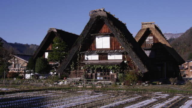 pan-up shot of buildings in a village of gassho-zukuri–style buildings from rice paddies in the foreground. this village of gassho-zukuri buildings... - satoyama scenery stock videos & royalty-free footage