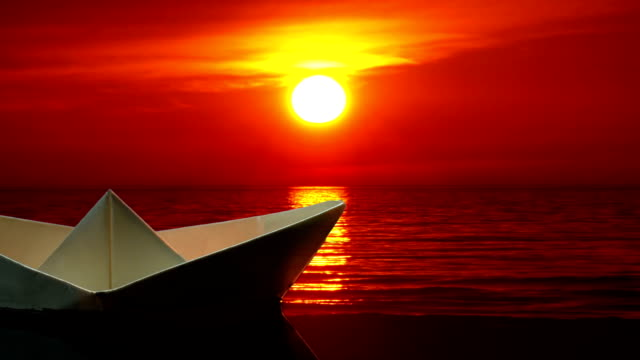 Paper boat at sunset