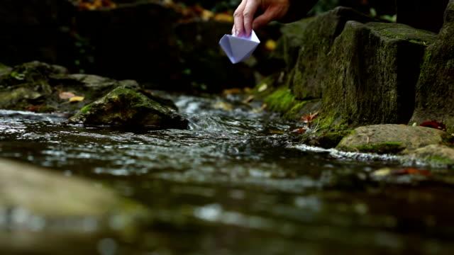 vidéos et rushes de papier bateau dans l'eau - origami
