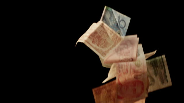 paper currencies fall past a black background. - lotterie stock-videos und b-roll-filmmaterial