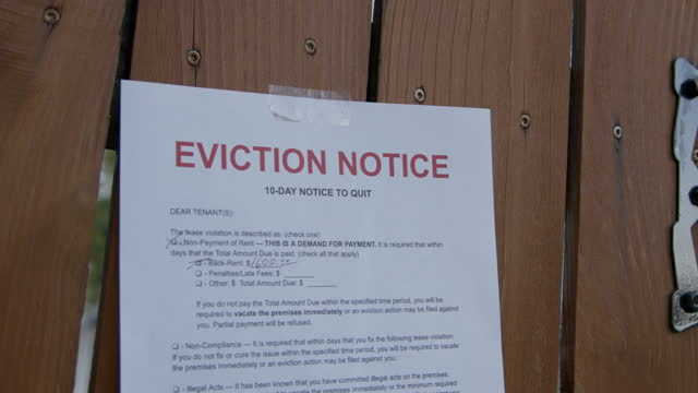 住宅郊外の賃貸住宅のフェンスゲートにテープで留めた紙立ち退き通知 - 住宅問題点の映像素材/bロール