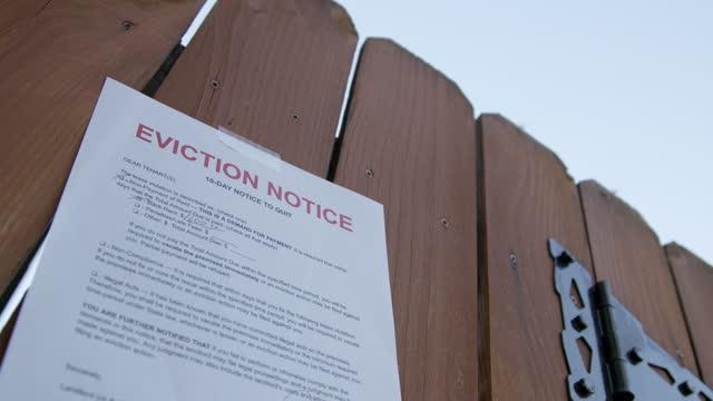 vídeos y material grabado en eventos de stock de aviso de desalojo de papel pegado a la puerta de la valla de una casa de alquiler en un barrio suburbano residencial - señal de información