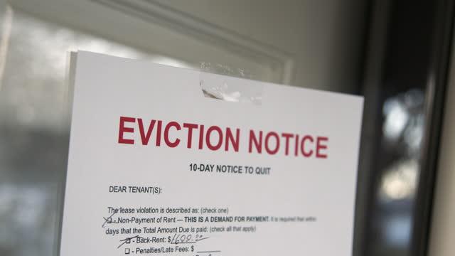 住宅郊外の賃貸住宅の正面玄関にテープで留めた紙立ち退き通知 - 住宅問題点の映像素材/bロール