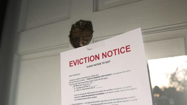 vidéos et rushes de avis d'expulsion papier enregistré à la porte d'entrée d'une maison de location dans un quartier résidentiel de banlieue - panneau d'information