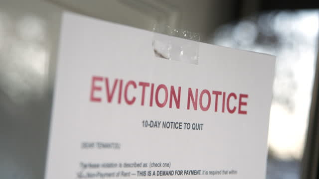 paper eviction notice taped to the front door of a rental home in a residential suburban neighborhood - information sign stock videos & royalty-free footage