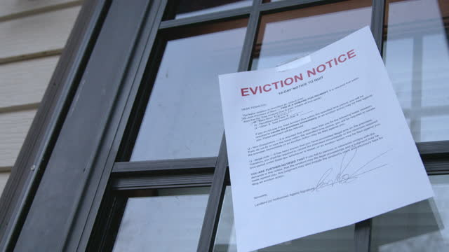 paper eviction notice taped to the front storm door of a rental home in a residential suburban neighborhood - information sign stock videos & royalty-free footage