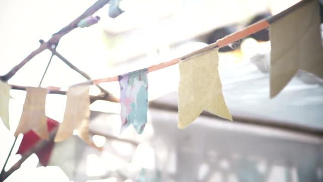 vídeos de stock, filmes e b-roll de bandeiras de papel pendurado com corda para festa ao ar livre. - bandeira