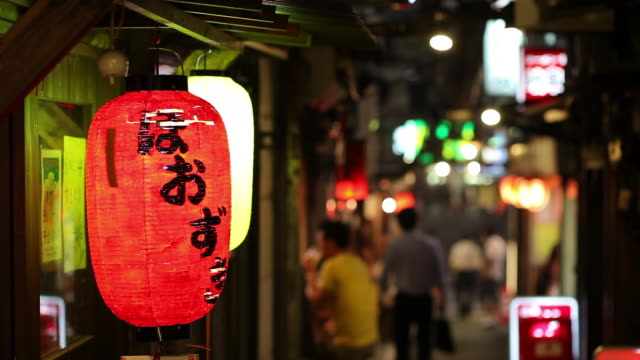 ms selective focus paper lantern hanging in street at night / tokyo, japan - ランプ点の映像素材/bロール