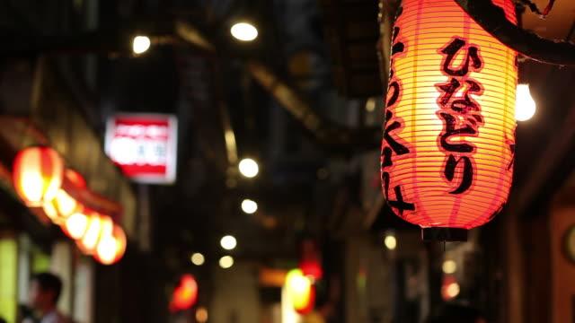 vídeos de stock e filmes b-roll de ms paper lantern hanging on narrow shopping street at night / tokyo, japan - lanterna de papel