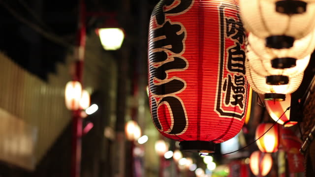cu selective focus paper lantern hinging on street at night / tokyo, japan - ランプ点の映像素材/bロール