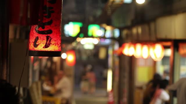 vídeos de stock e filmes b-roll de cu selective focus paper lantern hinging on street at night / tokyo, japan - lanterna de papel