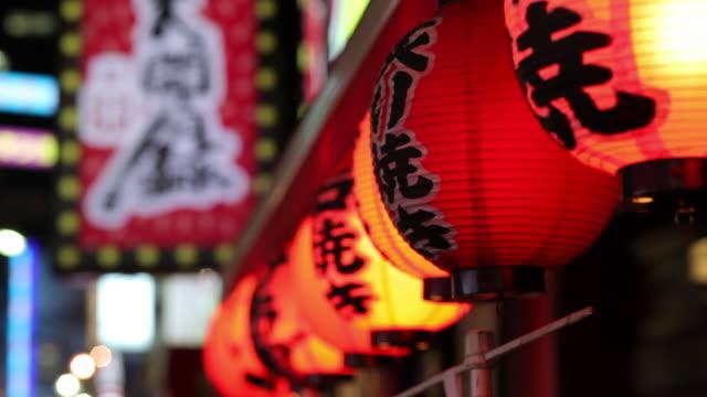 vídeos de stock e filmes b-roll de cu paper lanterns hanging on street at night / tokyo, japan - lanterna de papel