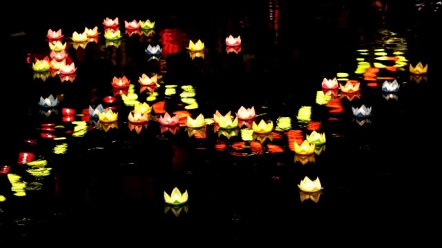 paper lanterns in water shines on the river at night during the festival of the birth of buddha. - lantern stock videos & royalty-free footage