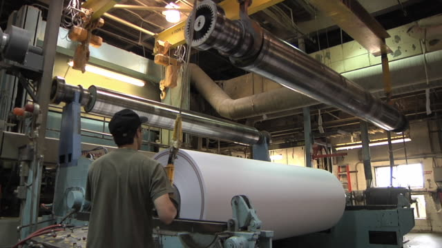 ms paper mill worker lowers new spindle into place in preparation for new roll of paper made from recycled paper / manistique, michigan, usa - paper mill stock videos and b-roll footage