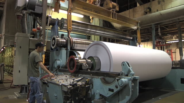 ms paper mill worker lowers new spindle into place in preparation for new roll of paper made from recycled paper / manistique, michigan, usa - paper mill stock videos & royalty-free footage
