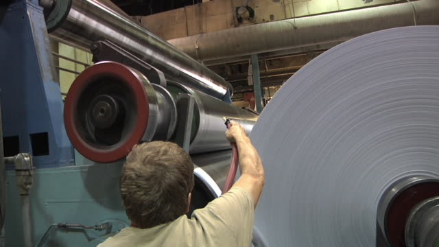 cu pan paper mill worker uses compressed air to cut new roll of paper / manistique, michigan, usa - paper mill stock videos and b-roll footage
