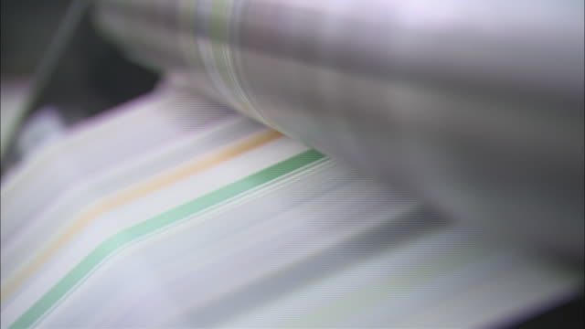 paper moves through a printing press. - 刊行物点の映像素材/bロール